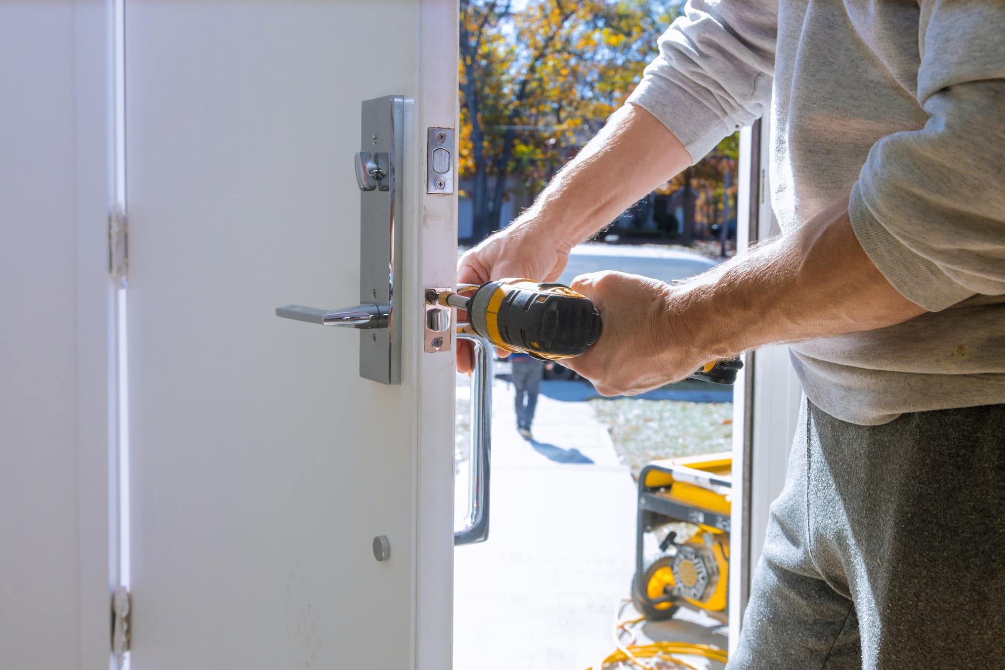 Here, one of our technicians uses a drill to install new door hardware.